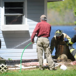 Bob Davis uses his garden hose Saturday to subdue a fire under his camp on Catfish Corner Road in Winslow. A wood stove ember caused the fire, according to the Winslow Fire Department.