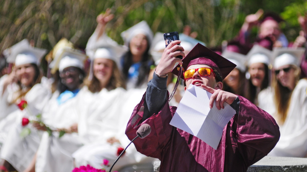 Standing at the lectern, Kevin Rodgers takes a selfie with his classmates before giving the senior address Saturday at the Kents Hill School graduation ceremony in Readfield.