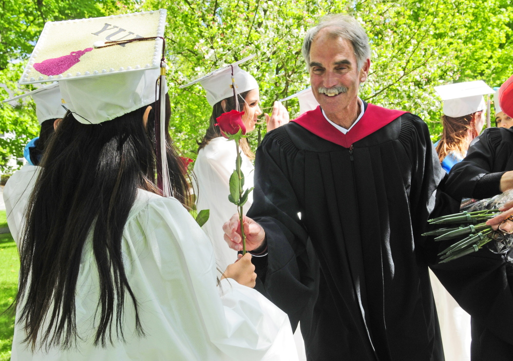 "Kents Hill School head of school Pat ""Mr. Mac"" McInerney hands out roses to senior girls before the school's graduation ceremony Saturday in Readfield."