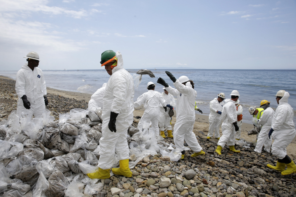 Clean up workers gather oil-contaminated sand bags at Refugio State Beach, north of Goleta, Calif.