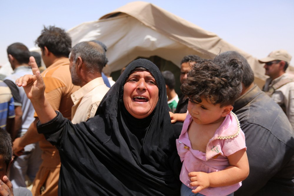 A women who fled Ramadi holds a child  in a camp in the town of Amiriyat al-Fallujah, west of Baghdad, Iraq, Friday.