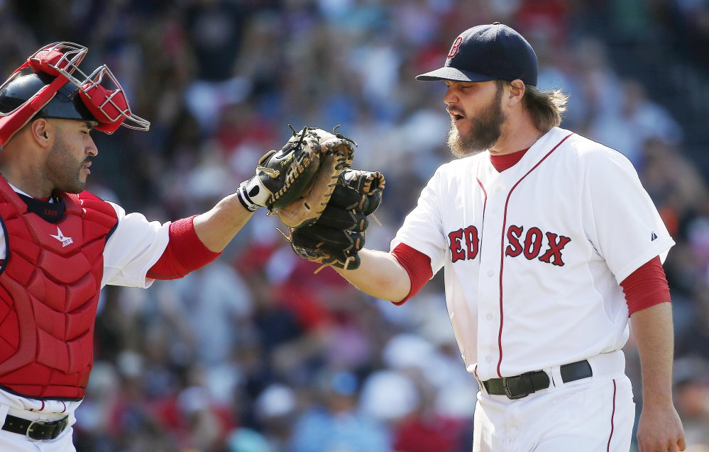Boston Red Sox's Wade Miley, right, taps gloves with Sandy Leon after pitching in the eighth inning Sunday against the Los Angeles Angels in Boston. The Red Sox won 6-1.