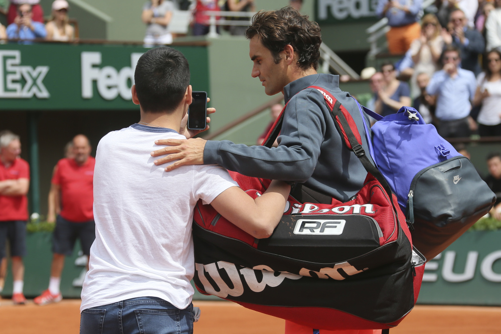 A boy who climbed down from the stands takes a selfie with Roger Federer on Sunday in the first round match of the French Open against Colombia's Alejandro Falla at the Roland Garros stadium, in Paris, France.
