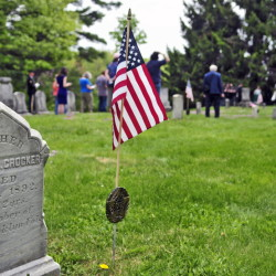 A flag marks Peleg Crocker's grave while Memorial Day ceremonies honor 44 Civil War veterans in Chelsea's Riverside Cemetery on Monday.