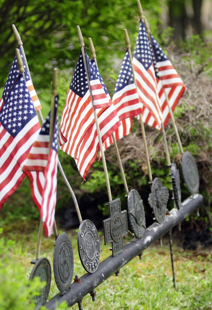 American flags and medallions for different wars front the Civil War monument during Memorial Day events on Monday in downtown Monmouth.