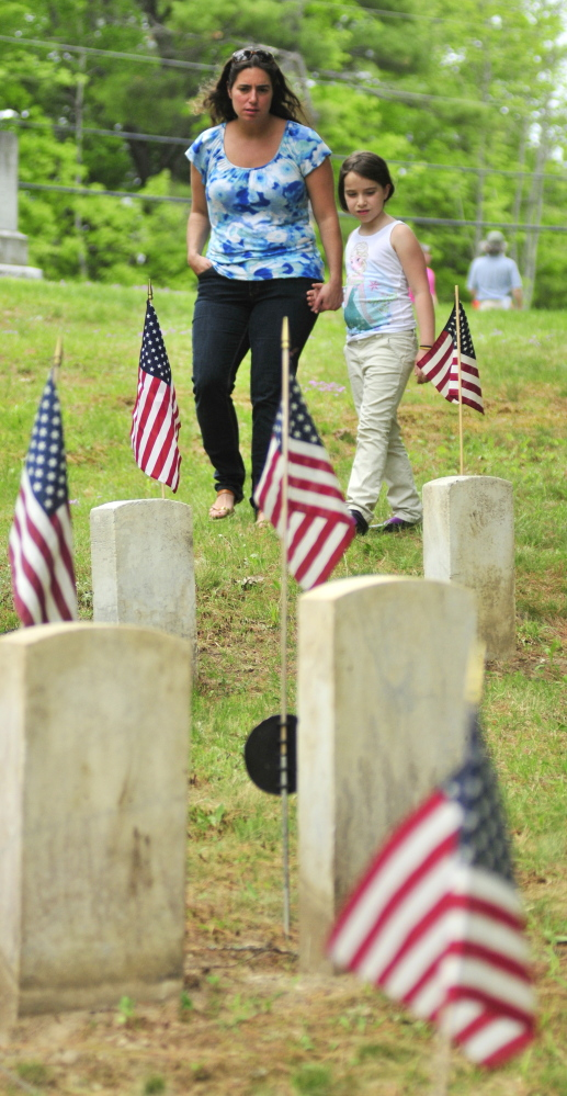 Amber Dostie, left, and her daughter, Maria Dostie, of Randolph, look at the names on a soldier's gravestone during Memorial Day ceremonies honoring 44 Civil War veterans on Monday in Chelsea's Riverside Cemetery.