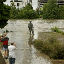 Water levels reach the base of a well-known statue of Stevie Ray Vaughan along the banks of Lady Bird Lake in Austin, Texas, Monday.