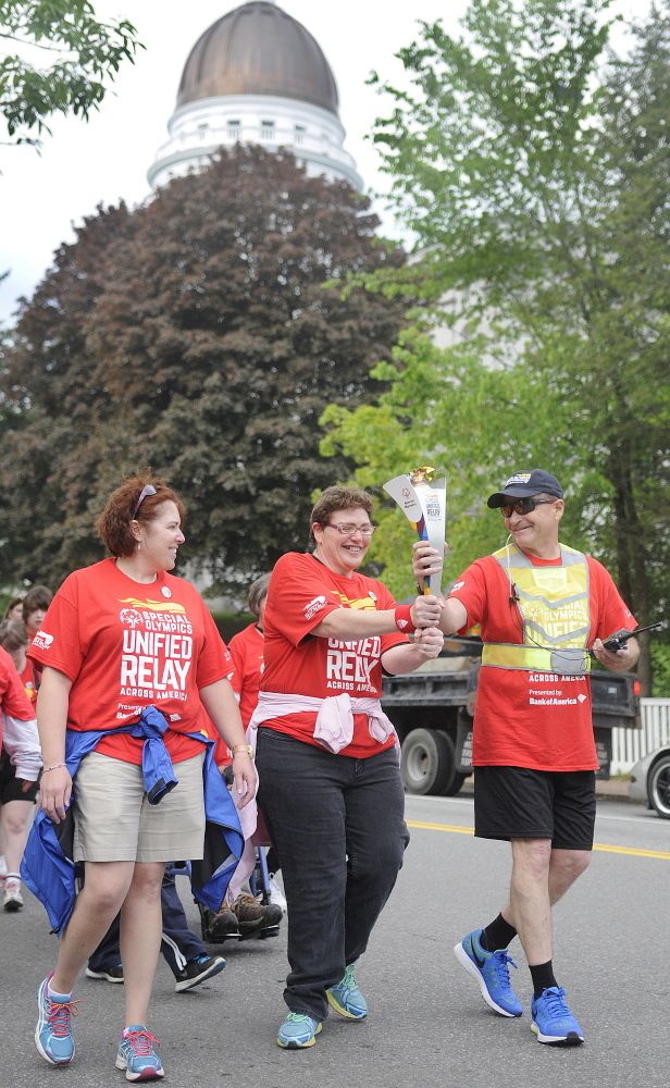 The torch is carried past the State House in Augusta on Tuesday on the first leg of the Law Enforcement Torch Run to raise funds for the Special Olympics.