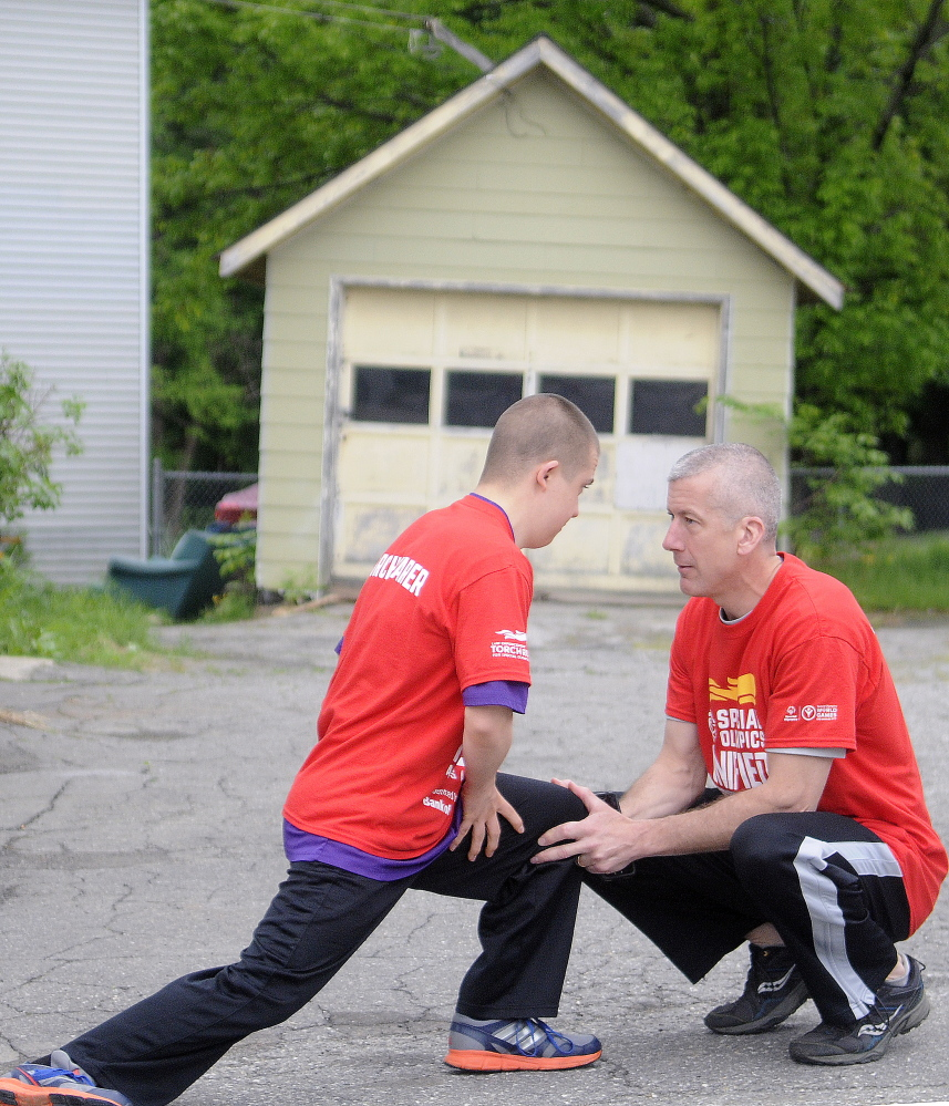 Special Olympian Zach Ewing stretches with his father, Orono Police Chief Josh Ewing, before running on the first leg of the Law Enforcement Torch Run in Augusta on Tuesday to raise funds for Special Olympics.
