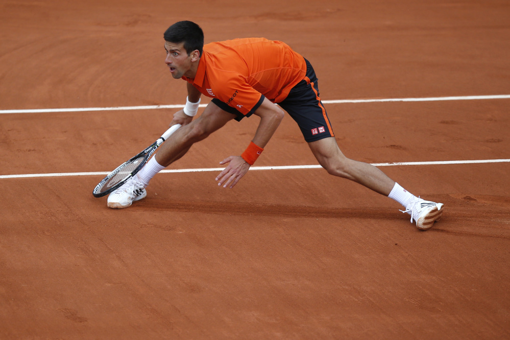 Serbia's Novak Djokovic eyes the ball after returning in the first round match of the French Open tennis tournament against Finland's Jarkko Nieminen at the Roland Garros stadium, in Paris, France, Tuesday.