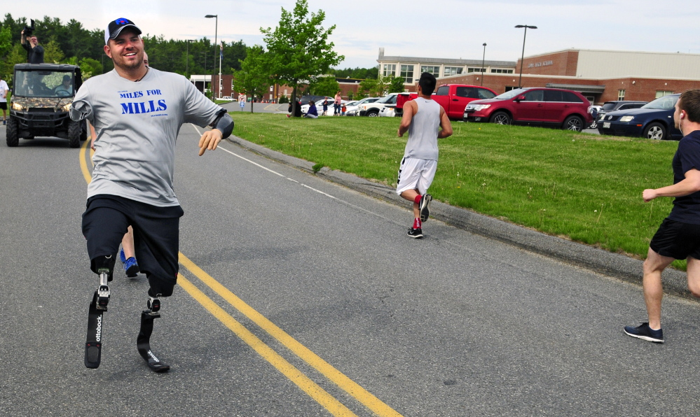 Travis Mills, of Manchester, waves to other participants as he takes part in the fourth annual Miles for Mills 5K on Monday at Cony High School in Augusta. Proceeds from the event will benefit the Travis Mills Foundation, a nonprofit organization, formed to benefit and assist wounded and injured veterans.