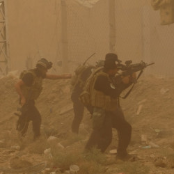 In this May 14, 2015 file photo, security forces defend their headquarters against attacks by Islamic State extremists during a sandstorm in the eastern part of Ramadi, the capital of Anbar province, Iraq.