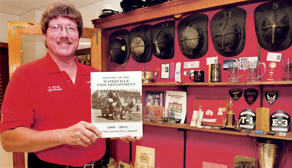 "Firefighter Lt. Scott Holst holds a copy of his book ""The History of the Waterville Fire Department, 1809-2015"" on Tuesday beside a case filled with department memorabilia at the fire station."