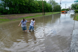 Danielle Crutcher and Joseph Morissette walk through the flood waters on Front Street in Waterville on Thursday.