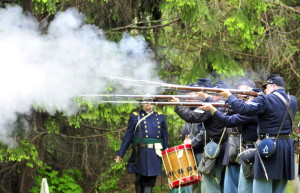 Civil War re-enactors fire a rifle volley during Memorial Day ceremonies honoring 44 Civil War veterans on Monday in Chelsea's Riverside Cemetery.