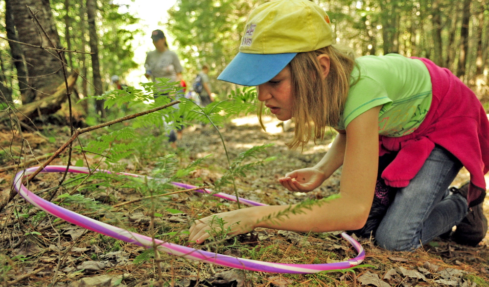 "During the ""map your kingdom"" exercise, Molly Anderson searches for what's inside the small circle of forest floor ringed by a hula hoop Friday during Forestry Day in the town forest around China's primary and middle schools. She and fellow student Kiera Grady then drew a map of what they found."