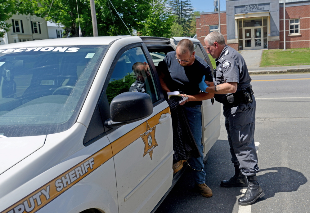Mark Bussell is put into a transport vehicle Friday by Correction Officer Charles Haley at Somerset County Superior Court in Skowhegan, bound for the Somerset County jail, where he will await transfer to state prison to serve his sentence for a manslaughter conviction.