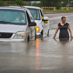 The Associated Press A city of Brownsville vehicle pushes a stranded van that attempted to make it through the high waters as a woman walks along side them along Mexico Boulevard in Brownsville, Texas, Thursday.