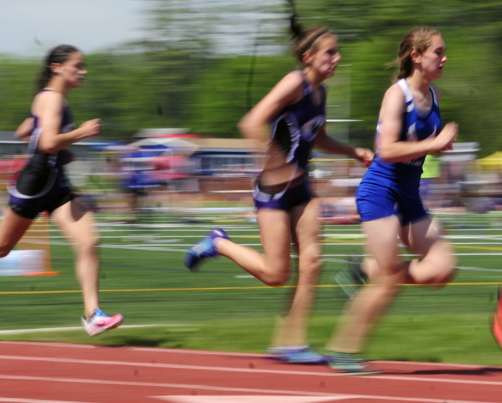 Erskine Academy's Kaylee Porter, left, runs the 800 meters during the KVAC track meet Saturday in Bath.