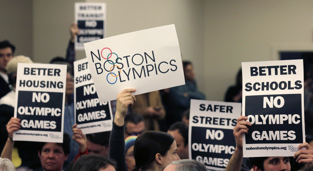 In this Feb. 5, 2015 file photo, members of the audience hold up placards against the Olympic Games coming to Boston, during the first public forum regarding the Boston 2024 Olympic bid in Boston.