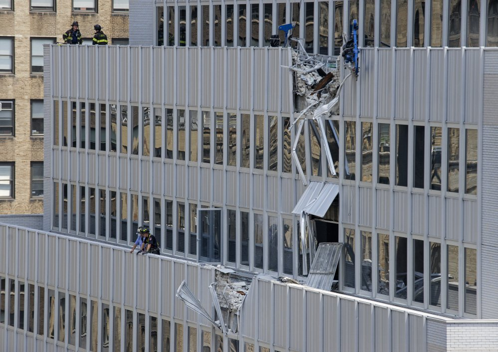 New York City firefighters stand near the damaged facade of 261 Madison Ave. after a piece of mechanical equipment being lifted by a crane broke free and fell about 28 stories to the sidewalk below, Sunday, in New York.