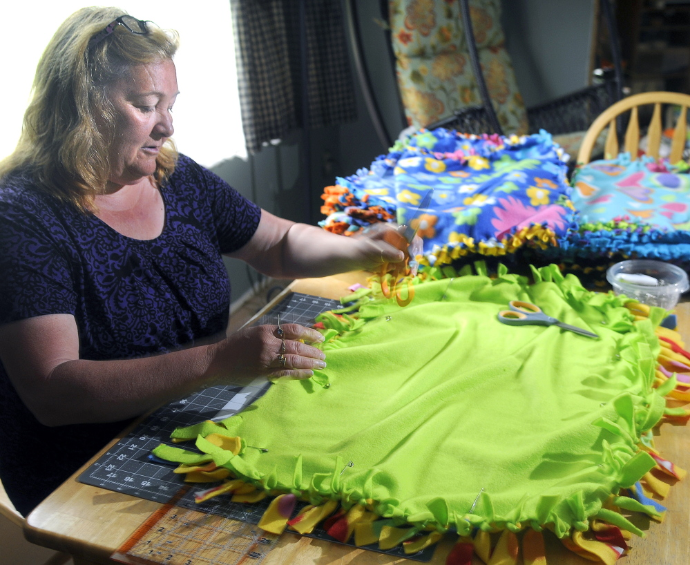 Judy Wildes works Sunday on a fleece quilt at her Augusta home. Wildes has donated more than 60 of the blankets for premature babies at Maine Medical Center in Portland after her grandson was born prematurely several months ago.