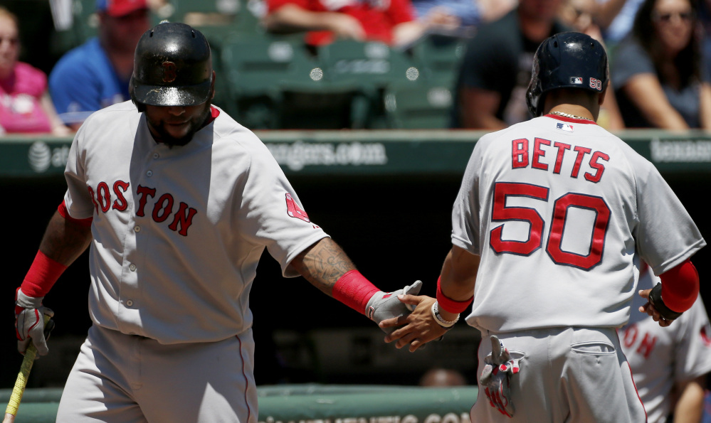 Boston Red Sox Mookie Betts is congratulated by Pablo Sandoval after scoring a run on an RBI single hit by Hanley Ramirez during the first inning Sunday against the Texas Rangers in Arlington, Texas. The Rangers won 4-3.