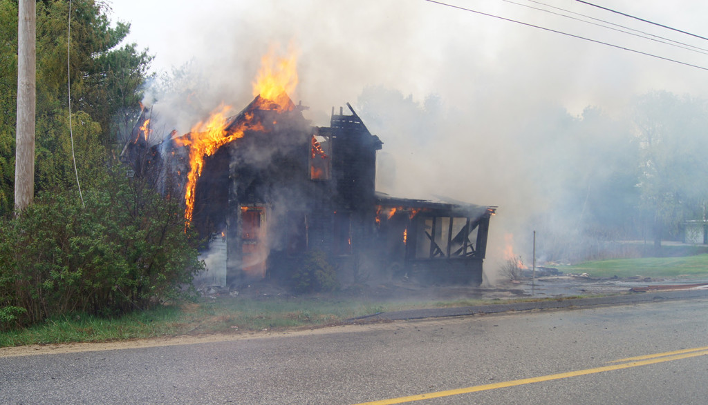 A vacant house owned by Paris Deputy Fire Chief Willie Buffington goes up in flames Monday during a permitted fire that got out of control. Chuck Blaquiere photo