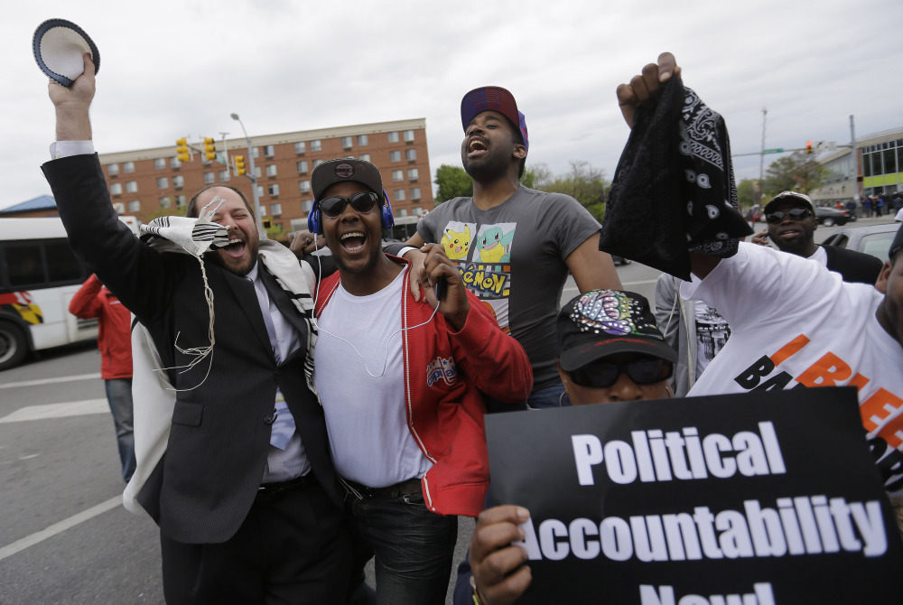 Rabbi Yerachmiel Shapiro, left, and other citizens celebrate on Friday after State's Attorney Marilyn J. Mosby announced criminal charges against all six officers suspended after Freddie Gray suffered a fatal spinal injury while in police custody in Baltimore.