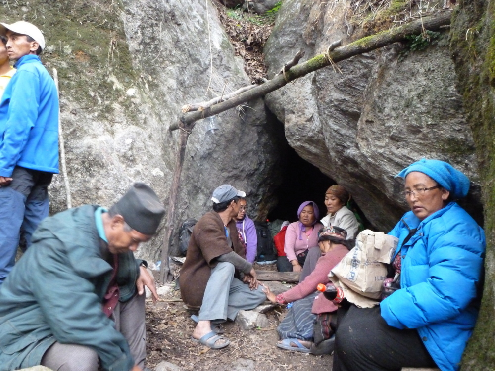Earthquake survivors sit at the entrance of a cave where they took shelter for one night from landslides. They left the cave the next day and set up camp outside. They cleared rocks to create a potential helicopter landing site, below, using flour to mark the site. After transmitting their coordinates to rescuers, they were eventually airlifted to safety.