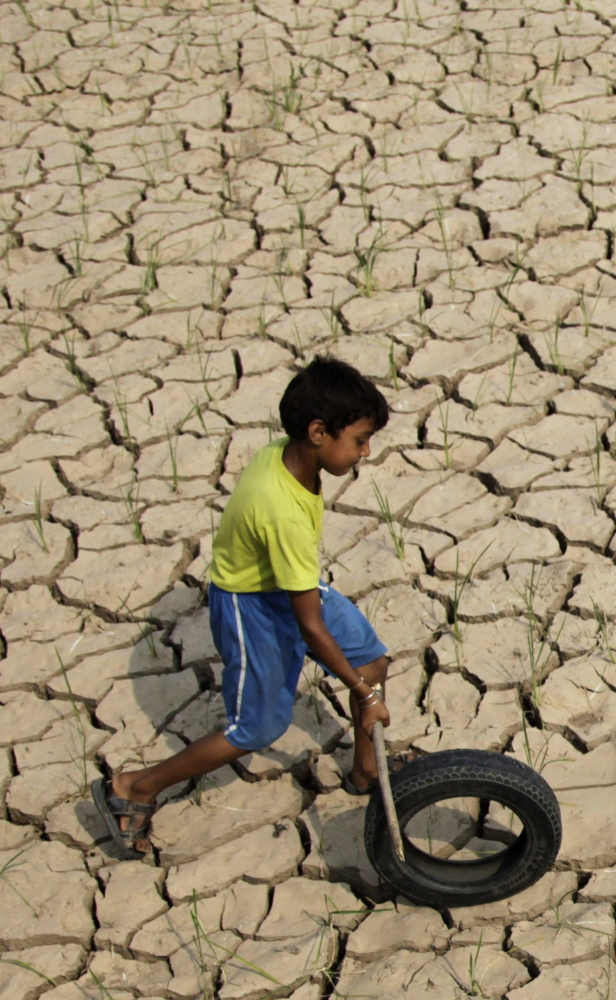 A boy plays on a parched rice paddy field in Ranbir Singh Pura, India, last year, when a delay in the monsoon season began raising fears that an El Nino drought was imminent.