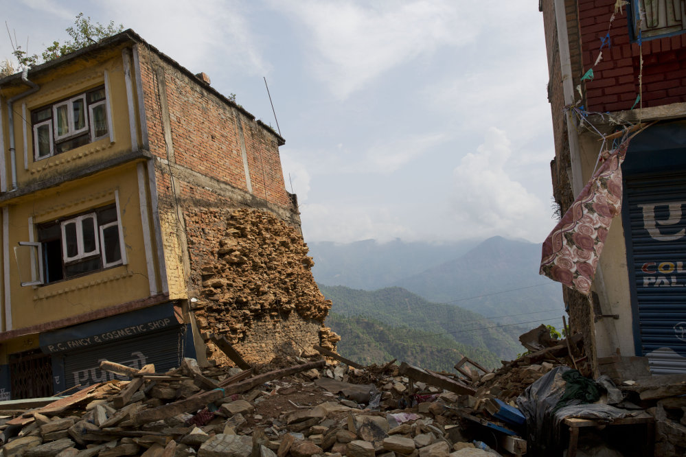 A building damaged in the May 12 earthquake stands tilted in Chautara, Nepal, on Wednesday. Thousands of fear-stricken people spent the night outdoors after a new earthquake killed dozens of people and spread more misery in Nepal, which is still reeling from a devastating quake that killed thousands nearly three weeks ago.
