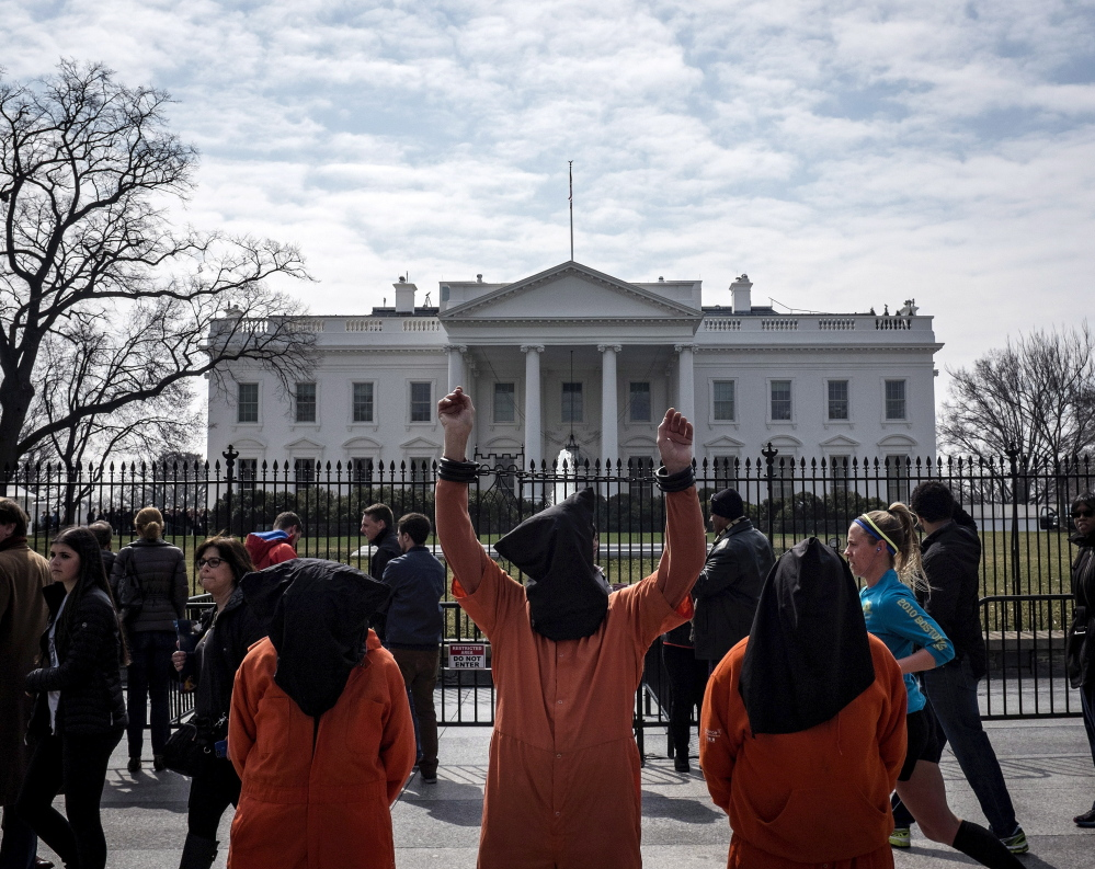 People dressed as Guantanamo Bay prisoners demonstrate in March. Sen. John McCain says he asked the White House for a plan to close the prison in 2009 but didn't get one.