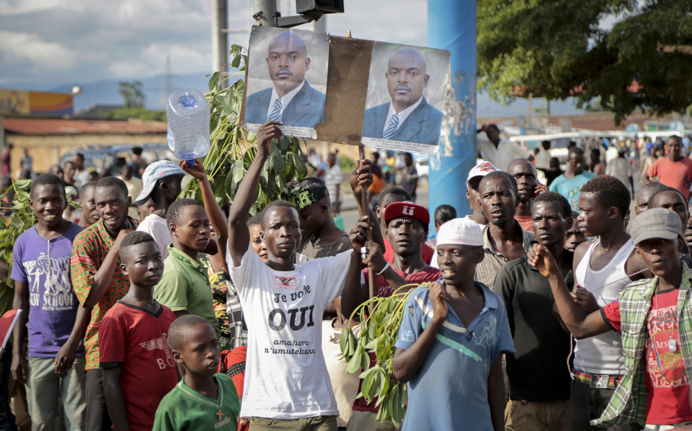 Supporters of Burundian President Pierre Nkurunziza hold photographs of him as they turn out to watch the presidential motorcade arrive in the Kamenge district of the capital, Bujumbura, on Friday.