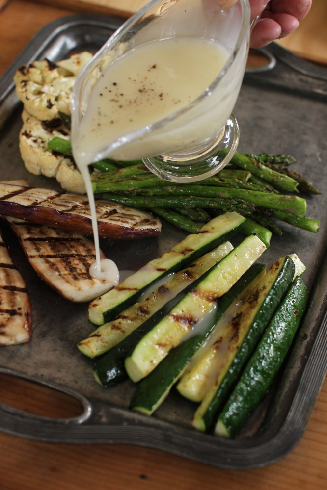 Grilled pork chops and asparagus with lemon-truffle vinaigrette. The Associated Press