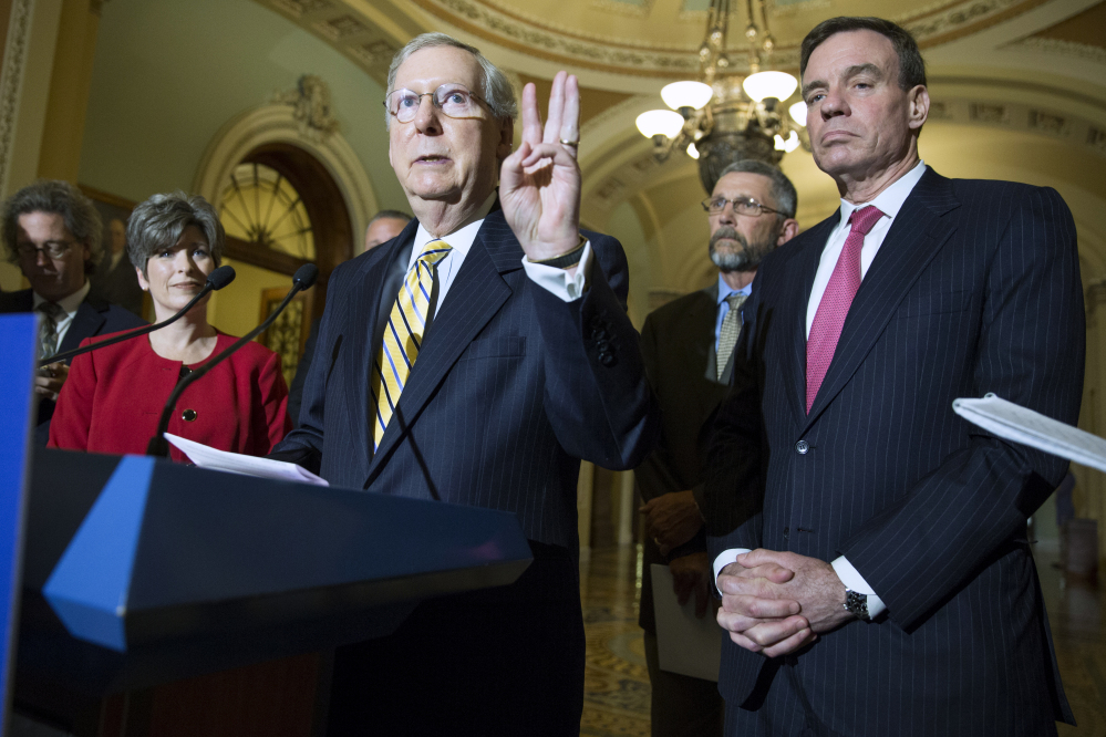 From left, Sen. Joni Ernst, R-Iowa, Senate Majority Leader Mitch McConnell of Ky and Sen. Mark Warner, D-Va., participate in a news conference on Capitol Hill in Washington, Tuesday, May 19, 2015, with small business owner to discuss the Trade Promotion Authority bill. (AP Photo/Evan Vucci)