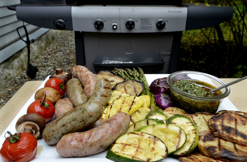 Grilled vegetables and sausages with a chimichurri sauce.