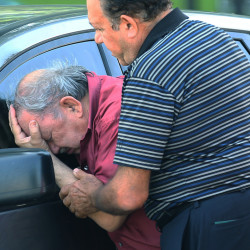 A man is comforted after finding out that a relative drowned in her truck in Houston on Tuesday. A holiday weekend of storms dumped record rainfall on the American heartland, causing major flooding.