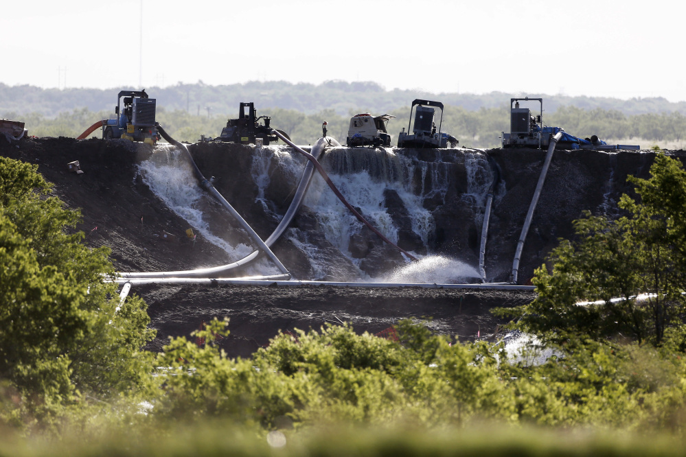 Workers attempt to relieve the pressure from the earthen dam at Padera Lake, Wednesday, in Midlothian, Texas.