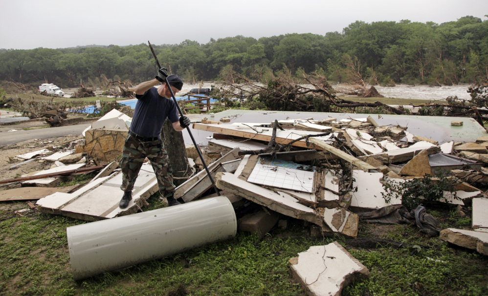 Kevin Calaway pries apart debris from a cabin shattered from a flood days earlier at a resort along the Blanco River, Tuesday, in Wimberley, Texas.