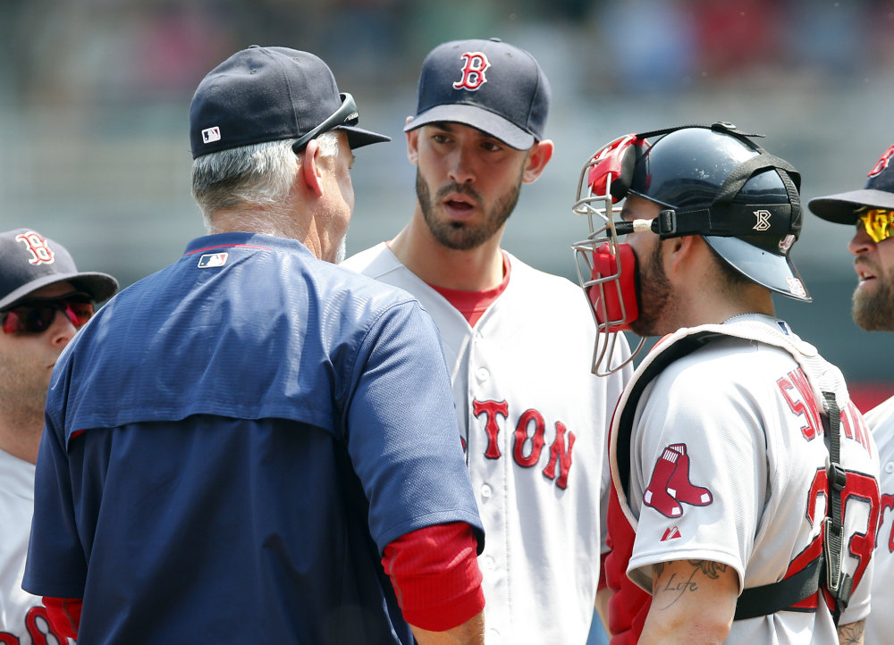 Red Sox pitching coach Carl Willis, left, talks with pitcher Rick Porcello after Porcello gave up an RBI single to the Twins' Joe Mauer in the third inning of Wednesday's game in Minneapolis. Porcello allowed six earned runs in seven innings.