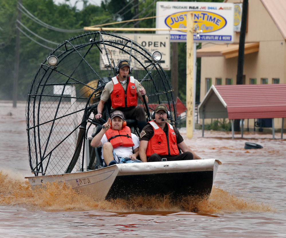 Highway patrolmen rescue Justin Nimmo, left, from his business, Just-In-Time, after flooding caused by rising water from Saturday night's storms trapped him in the store on Sunday, May 24, 2015 in Purcell, Okla.