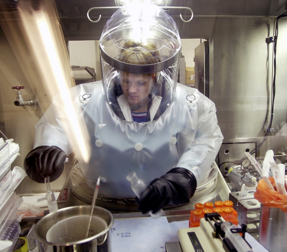 Microbiologist Ruth Bryan works with BG nerve agent simulant in an airtight enclosure also used for hands-on work with anthrax at Dugway Proving Ground in Utah.