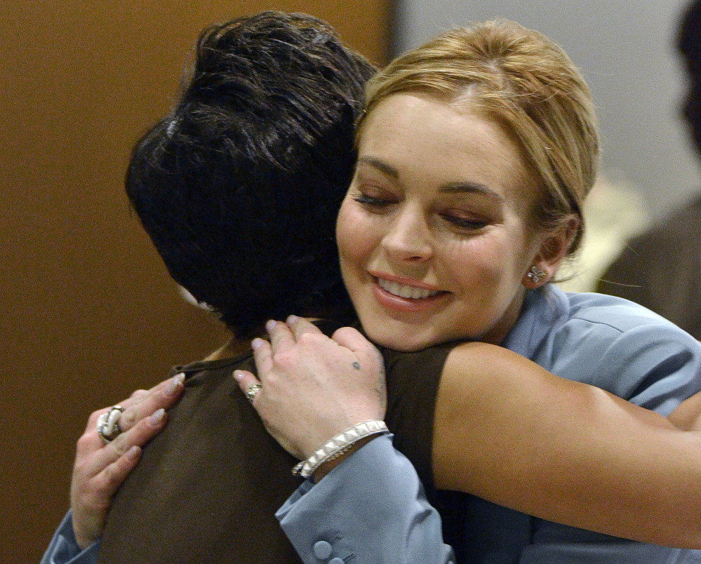 Lindsay Lohan embraces her attorney, Shawn Holley, after a progress report on her probation for theft charges in Los Angeles Superior Court in 2012.
