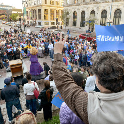 "Paul Revier of Portland gives the peace sign from the monument in Monument Square during Thursday's ""We Are Maine March & Rally"" in downtown Portland. The march was organized by the Maine Immigrants' Rights Coalition. Participating organizations included the ACLU of Maine, Bet Ha'am synagogue's Social Action Committee, Frannie Peabody Center, the Maine Council of Churches and the African Immigrant Association."