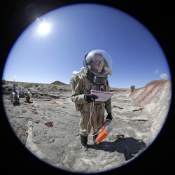 Auriane Canesse, crew geologist and health and safety officer, of Crew 153, takes magnetic readings of the ground using a large rectangular apparatus near the Mars Desert Research Station.