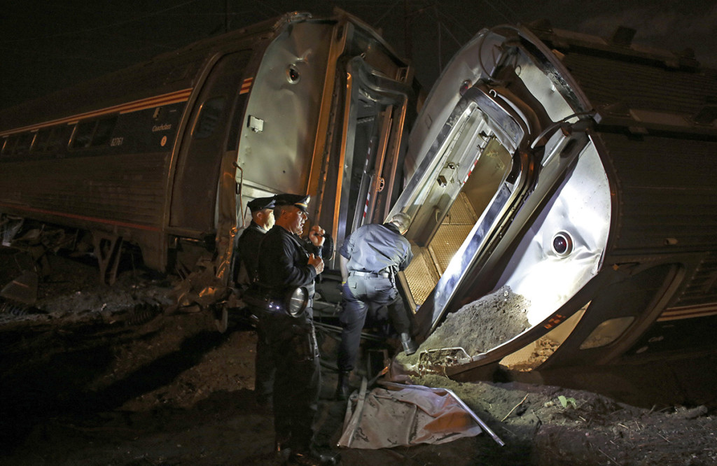 Emergency personnel comb the wreckage of Amtrak train 188 in this  May 12, 2015, photo. The train derailed in Philadelphia on its run to New York City, killing eight and injuring 200 people. Amtrak says it will install video cameras inside locomotive cabs that record the actions of train engineers. The Associated Press