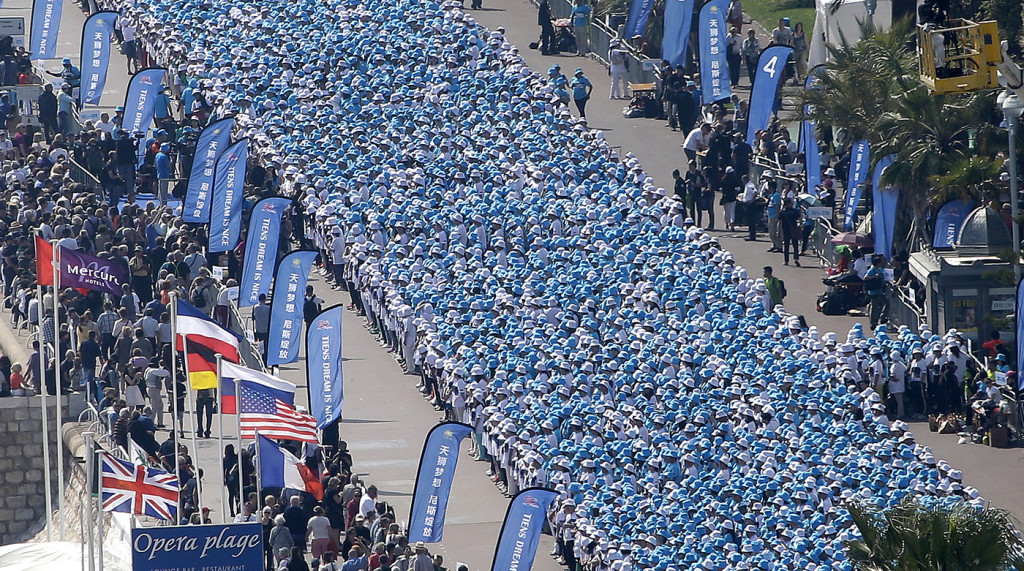 Employees of the Tiens Group take part in a parade in Promenade des Anglais, Nice, on Friday that was financed by CEO Li Jinyuan as part of a four-day celebration weekend for the 20th anniversary of his company. The Associated Press