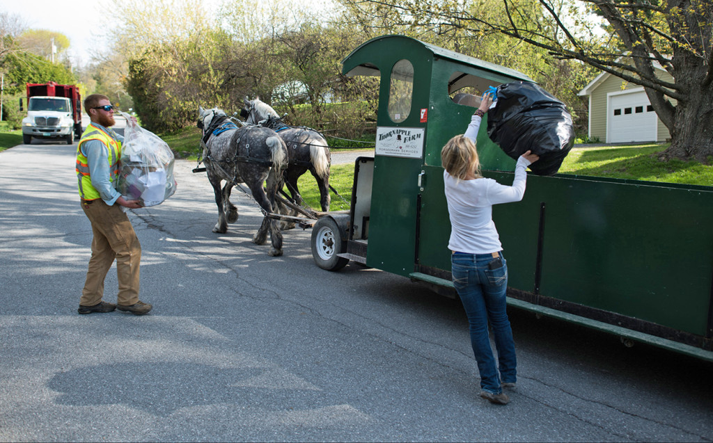 Nick Hammond, left, and Amanda Morse collect garbage and recycling in Middlebury, Vt. Patrick Palmer's horse-drawn garbage collection business has clip-clopped through the sleepy village of Bristol collecting trash for 18 years. Now he is training Hammond and Morse to collect trash with a team of draft horses in the busier college village of Middlebury. The Associated Press