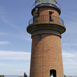 In this Aug. 27, 2009, photo, President Barack Obama, left, walks around Gay Head Lighthouse while on vacation on Martha's Vineyard in Aquinnah, Mass. The lighthouse is being moved to prevent it from falling off its rapidly eroding cliffside perch. The Associated Press